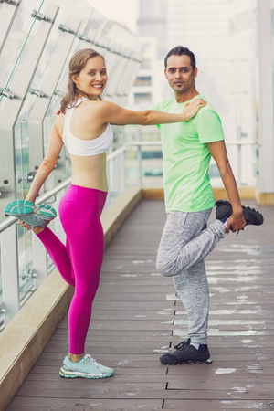 Smiling young sporty woman and man stretching legs