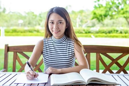 learning by doing: Happy Asian female student doing homework outdoors