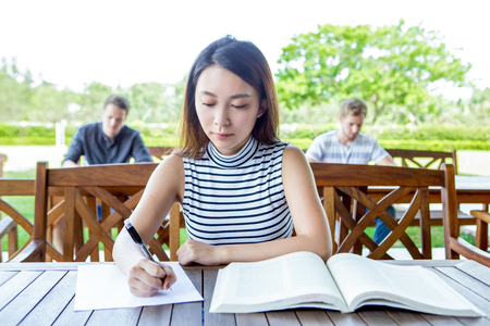 Serious Asian female student doing test outdoors Stock Photo