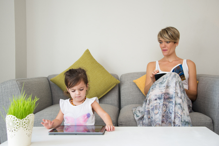 Concentrated daughter using tablet at coffee table