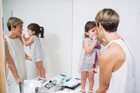 bathroom mirror: Cute daughter applying lipstick on mothers lips Stock Photo