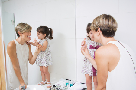bathroom mirror: Mother and daughter preparing for stroll