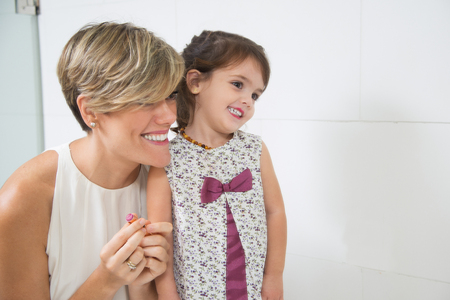 Happy mother and daughter looking in mirror