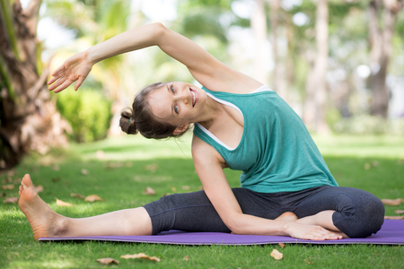 Mujer joven feliz que estira en la estera del ejercicio