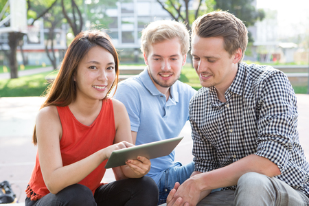 Positive Asian woman using tablet with groupmates Stock Photo