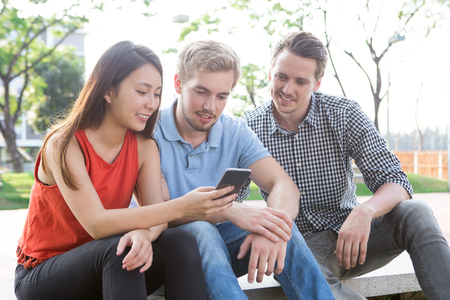 Positive friends watching video on smartphone