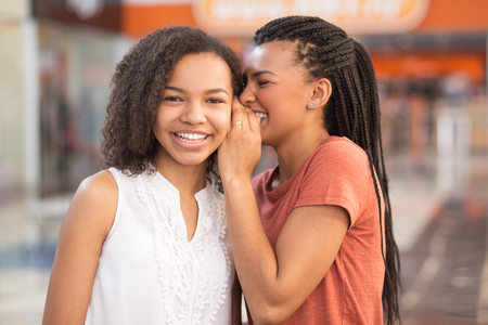 Close-up van Twee Mooie Zwarte Meisjes Delen Geheimen Stockfoto - 77911867