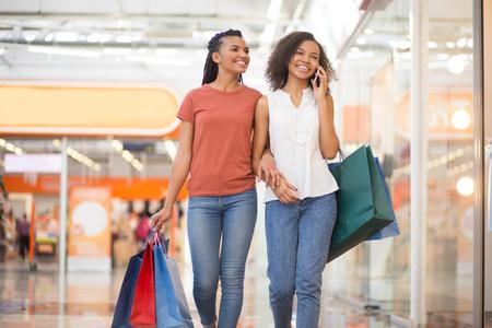 Ontspannen zwarte meisjes lopen in het winkelcentrum