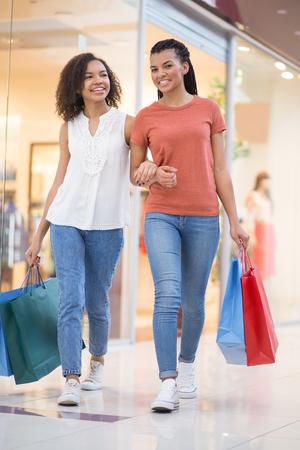Two Carefree Black Girls Walking in Shopping Mall