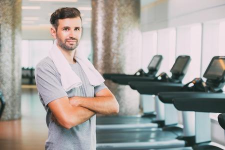 Jeune homme sportif avec une serviette sur le cou dans la salle de gym Banque d'images - 77910684