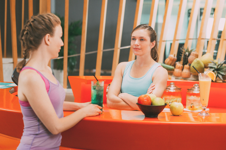 Two Young Women Talking at Sport Bar Counter