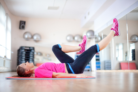 Positive young woman doing exercise on mat in gym