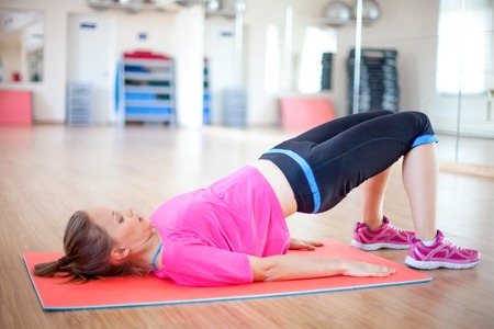 Serious woman doing abdominal exercise on mat