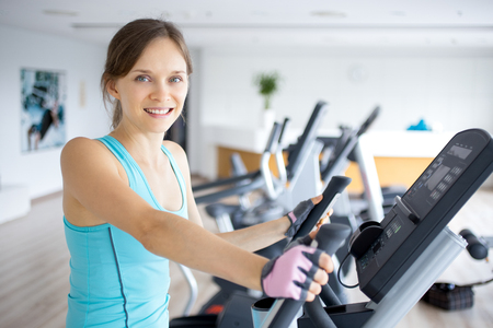 Smiling Girl Training on Exercise Machine in Gym