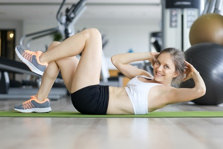 situp: Happy young woman doing crunches on mat in gym