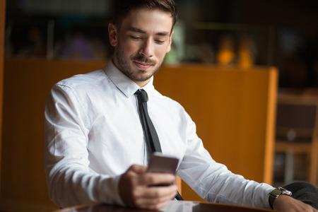 Successful businessman using wi-fi in lobby 写真素材