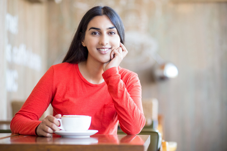 Optimistic female student with coffee cup