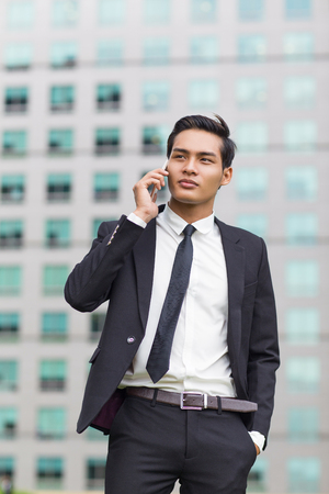 hands pocket: Asian Business Man Calling on Phone Outside