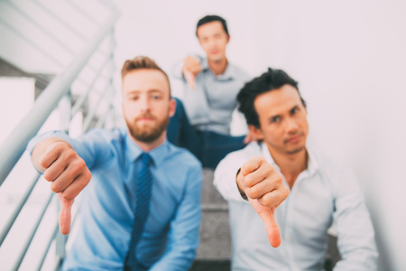 Group of multiethnic men showing thumb down Stock Photo