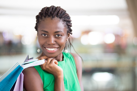 Happy face of young woman holding shopping bags