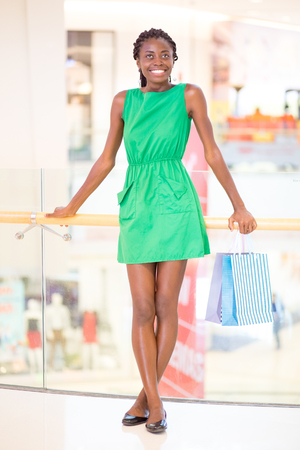 Smiling woman posing with bags in shopping mall