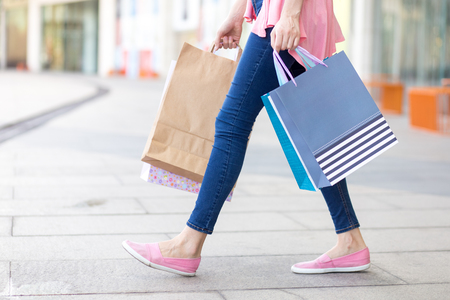 Jonge Kaukasische vrouw die met het winkelen zakken loopt