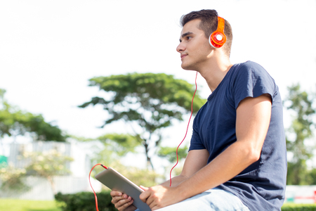 Aspirated man using tablet to listen to music