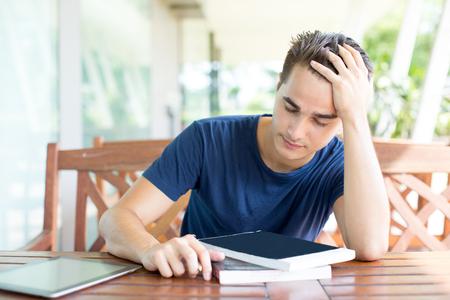 Uitgeputte jonge studentenzitting bij bureau