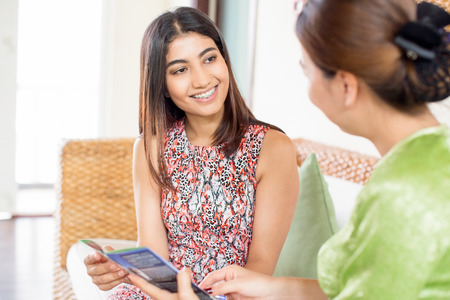 Smiling young woman talking to friend indoor Stockfoto