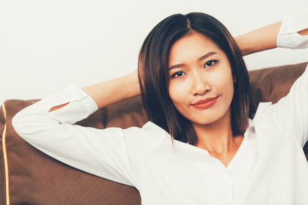 Closeup of Content Asian Woman Resting on Cushion Stock Photo