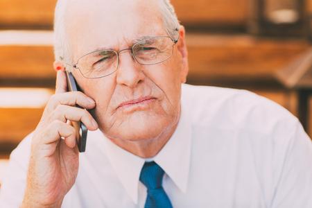 Serious Senior Businessman with Smartphone Stock Photo