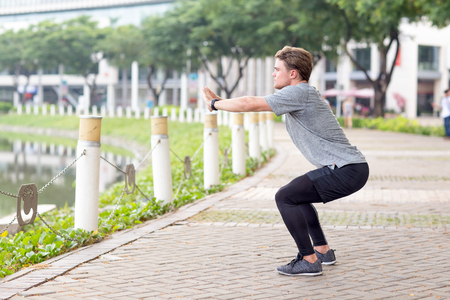 Serious Sporty Man Doing Squats Outdoors