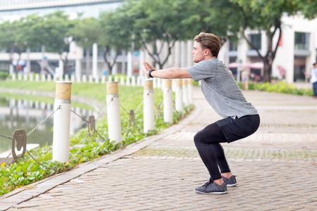 Ernstige sportieve man doet squats buitenshuis