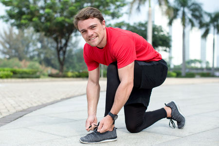 Smiling Sporty Man Tying Shoelaces Outdoors Stock Photo