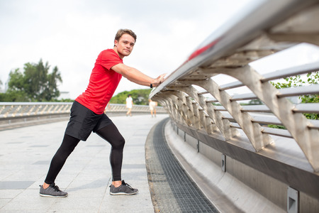 Sporty Man Stretching Calf and Leaning on Railing