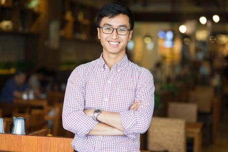 Portret van gelukkige jonge Aziatische zakenman in café Stockfoto