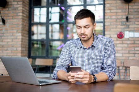Inhoud Man lezing bericht op Smartphone in Cafe Stockfoto - 79806230
