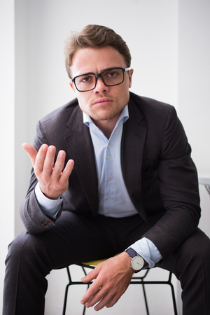 indignant: Indignant young businessman gesturing to camera Stock Photo