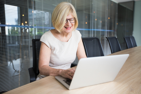 jalousie: Smiling Senior Lady With Laptop in Conference Room