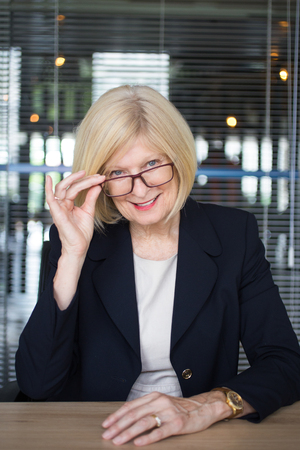 coquettish: Smiling Senior Business Lady Looking Over Glasses Stock Photo