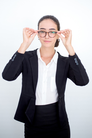 Serious female manager trying on new glasses