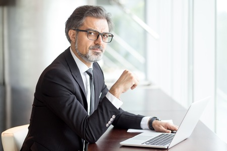 Intelligent handsome man with laptop in cafe