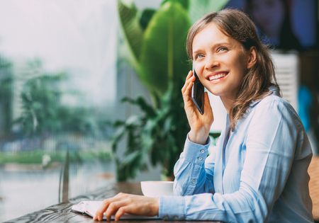 Cheerful female manager talking on phone in cafe