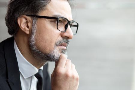 Contemplative senior man touching beard