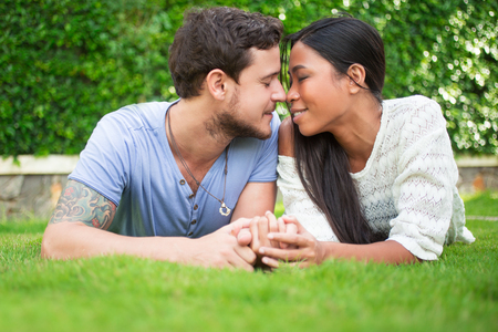 touching noses: Couple Lying on Grass and Touching Noses Stock Photo