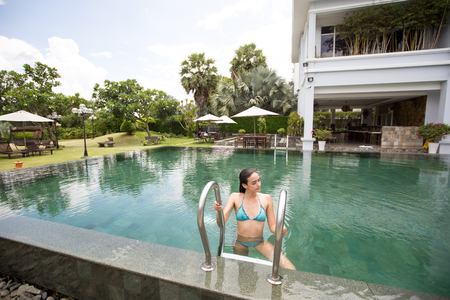 Smiling woman climbing out of outdoor hotel pool