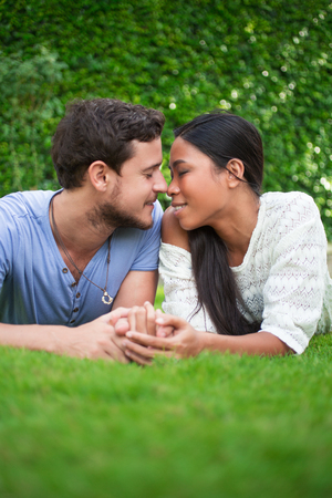 touching noses: Couple Resting on Grass and Touching Noses Stock Photo