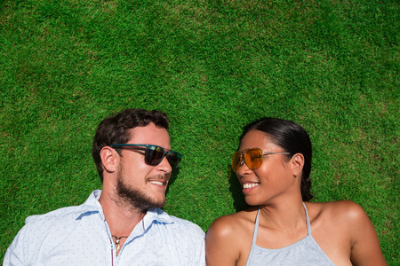 Joyful Young Interracial Couple Resting on Lawn Stock Photo