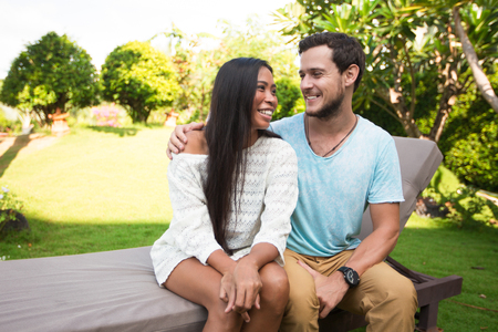 tenderly: Happy Couple Hugging Tenderly on Chaise Longue Stock Photo
