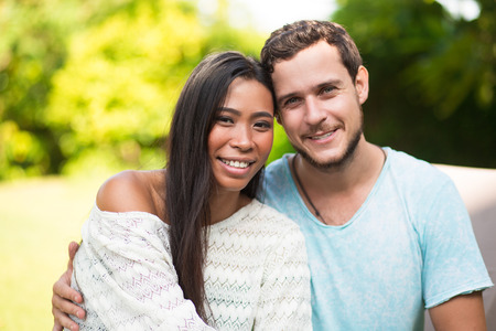 tenderly: Smiling Interracial Couple Embracing Tenderly Stock Photo